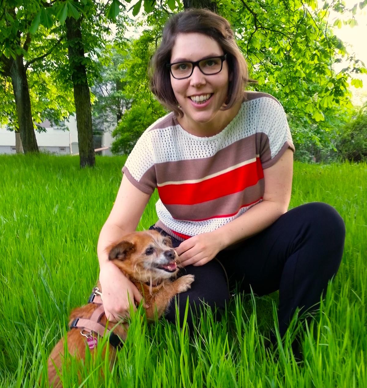 Kniende Frau mit Hund auf einer Wiese