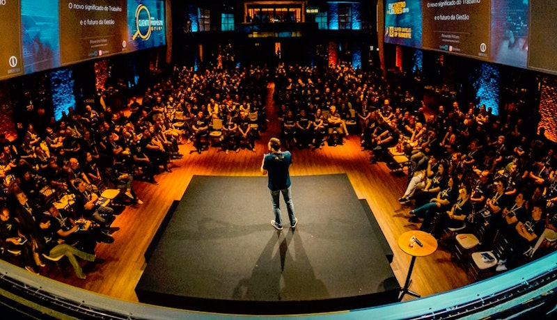 Mann auf einer Bühne vor Zuschauenden